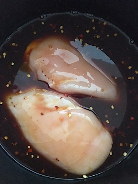 Raw chicken breasts in the crockpot with marinade that will turn into Crockpot Bourbon chicken by crockpot empire