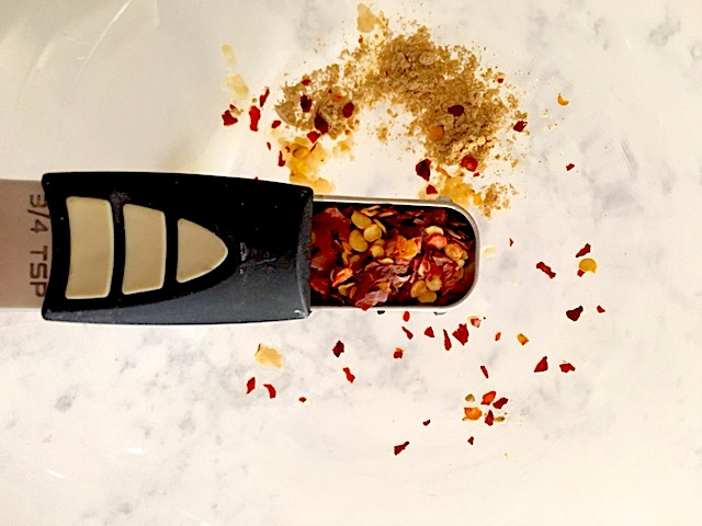 Crushed red pepper flakes in an adjustable measuring tool