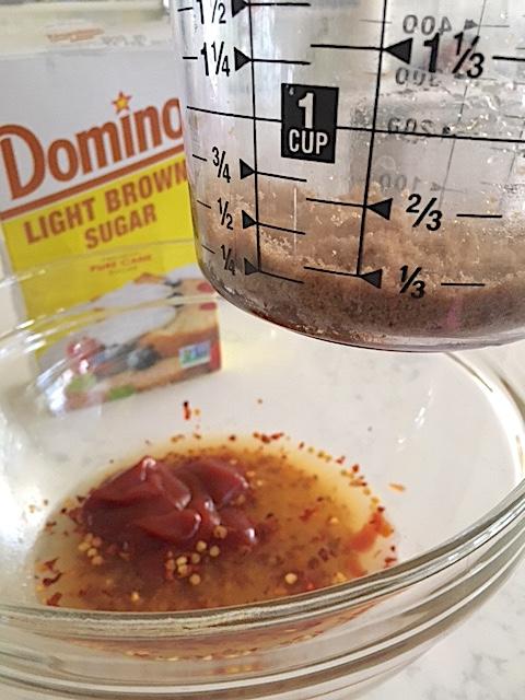 Domino Light Brown Sugar in measuring cup going into marinade for Crockpot Empire bourbon chicken recipe
