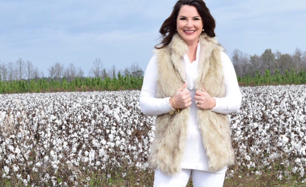 Kim Bishop in a cotton field wearing a neutral faux fur vest