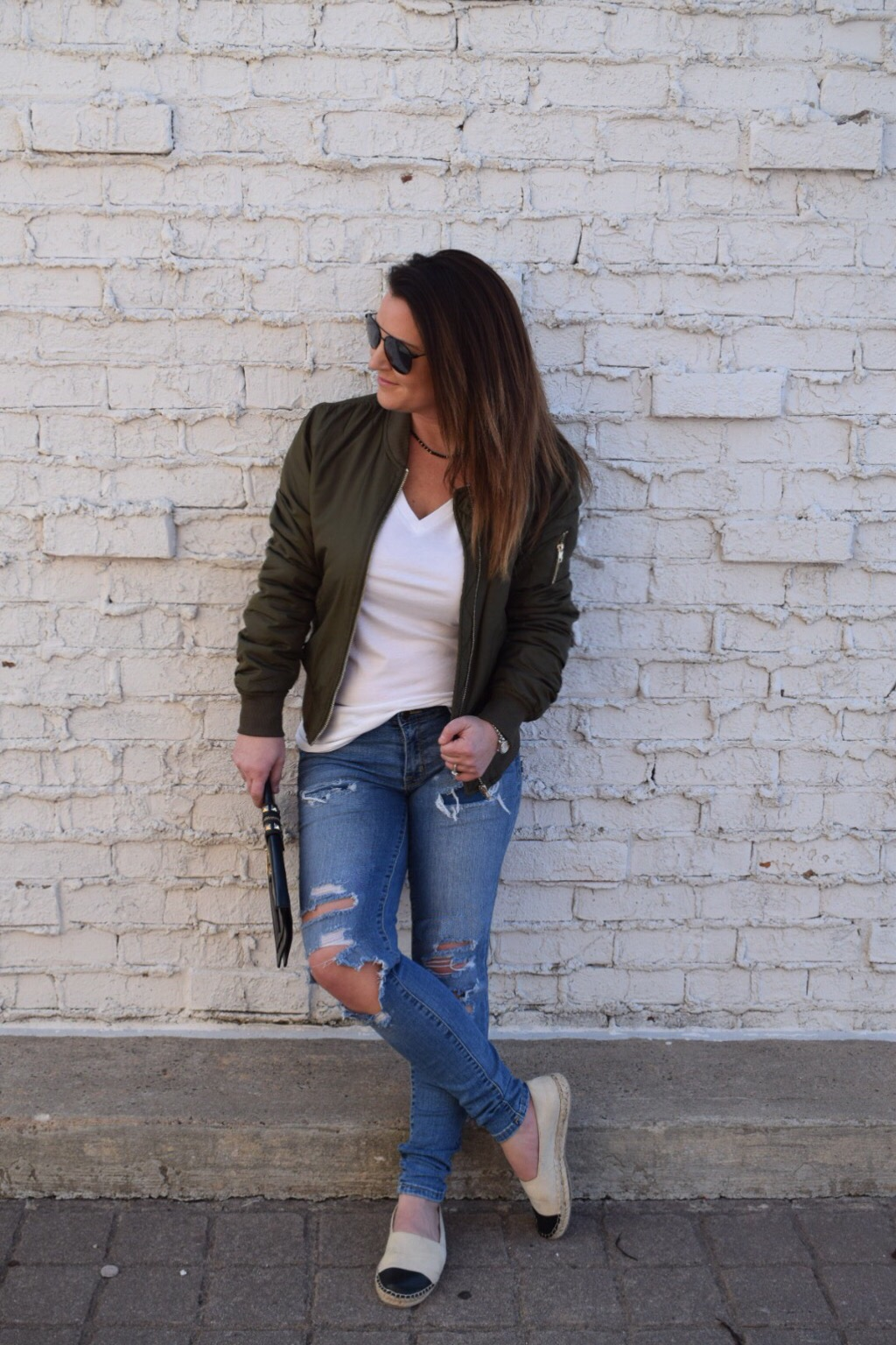 Olive bomber jacket with destroyed denim a white tee canvas espadrilles and black aviators