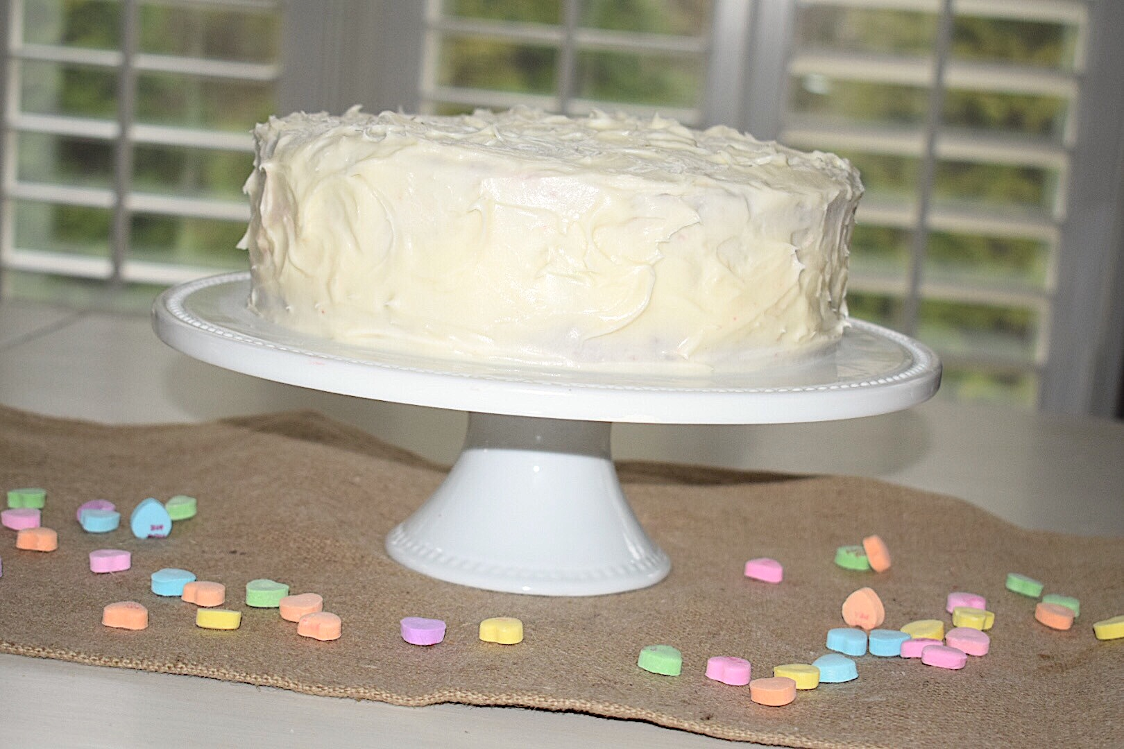 A homemade red velvet cake with white cream cheese frosting on a white cake plate with conversation hearts