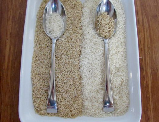 Uncooked brown and white rice side by side with spoons