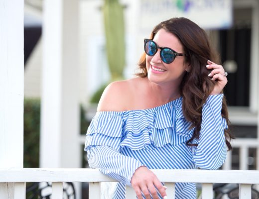 Kim Bishop in a blue striped ruffle one shoulder top with mirrored sunglasses